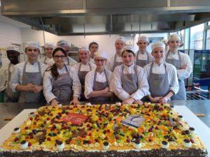 Leerlingen hotel bakken taart voor 125 personen