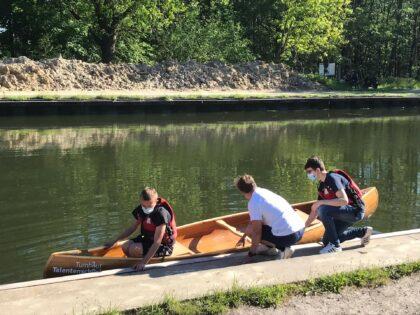Leerlingen Hout laten zelfgebouwde kano te water